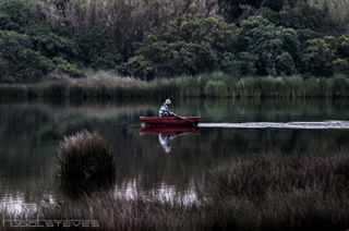 red boat photo man green river fisherman
