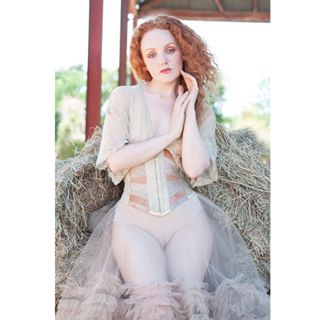 corsetry paleskin ivoryflamemodel timelessbeauty redhead ivoryflame farmstead haybales corsets editorialphotography editorial classicbeauty tenderness orchidcorsetry