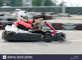 sport driving carts fun racer competition blurred race motion action driver enjoyment carting racing female cart woman circuit speed kart fast helmet blur